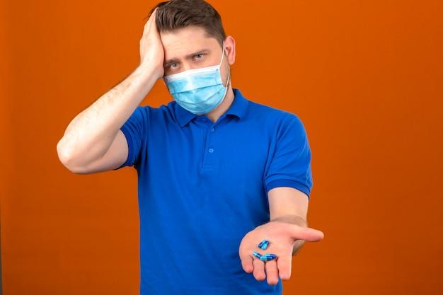 Jeune homme vêtu d'un polo bleu en masque de protection médicale à la recherche de malaise et de malade debout avec la main sur la tête souffrant de maux de tête tenant des pelures dans la main ouverte sur un mur orange isolé