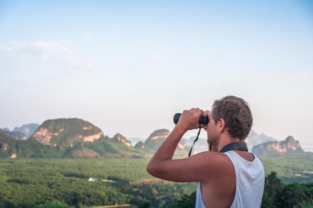 Un jeune homme vêtu d'un t-shirt blanc regarde du haut au loin à travers des jumelles dans le contexte de la faune, du ciel, des montagnes et de la mer.