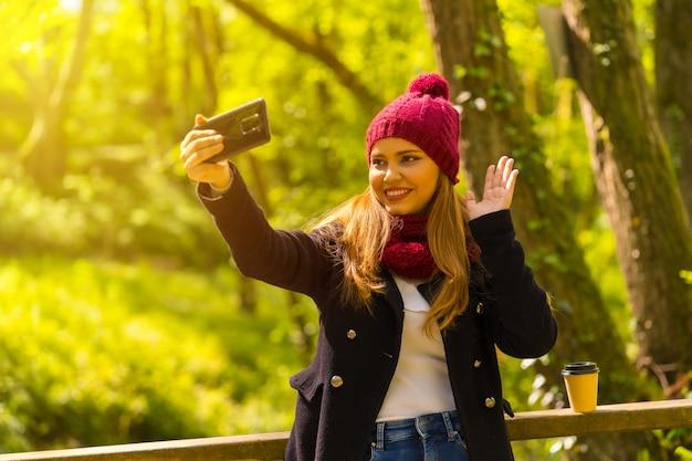 Jeune homme vêtu d'une veste noire, d'une écharpe et d'un bonnet de laine rouge profitant d'un parc en automne, saluant lors d'un appel vidéo avec le téléphone