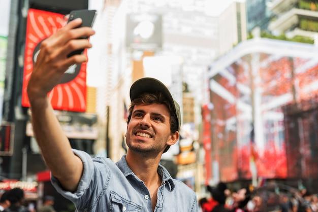 Jeune homme en ville prenant selfie
