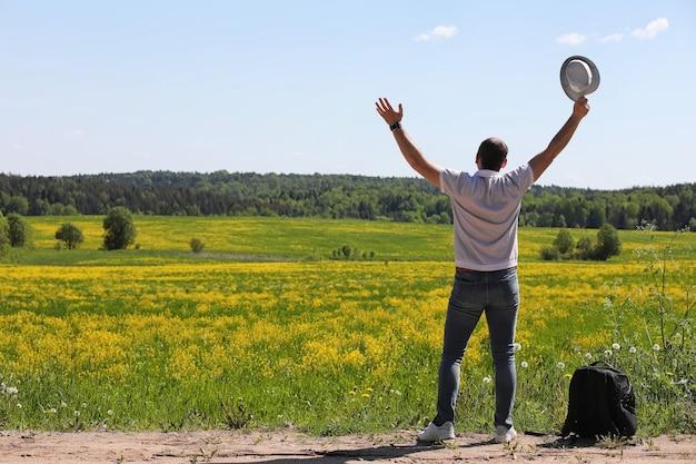 Le jeune homme voyage avec un sac à dos un jour d'été dehors