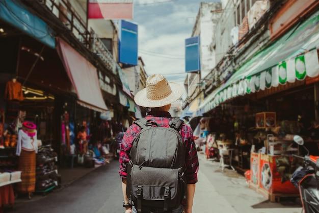 Jeune homme voyageant backpacker avec chapeau marchant dans la rue piétonne.