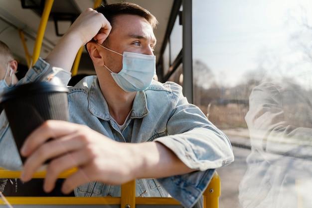 Jeune homme voyageant en bus de la ville tenant une tasse de café