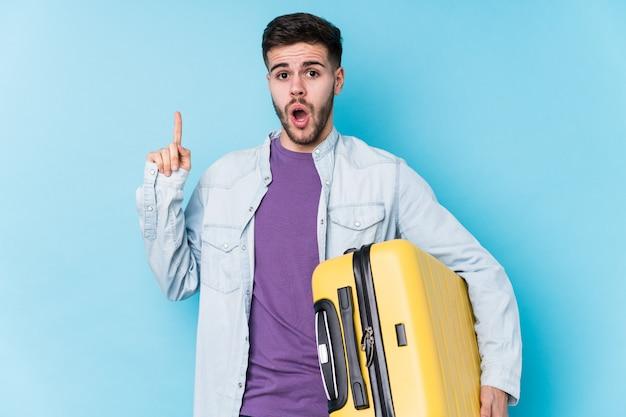 Jeune homme voyageur caucasien tenant une valise ayant une excellente idée