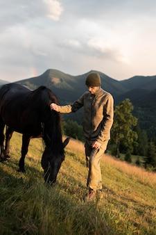 Jeune homme voyageur debout à côté d'un cheval