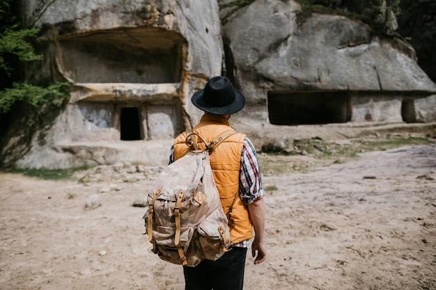 Un jeune homme voyageur explore les ruines d'une ville troglodyte dans les montagnes