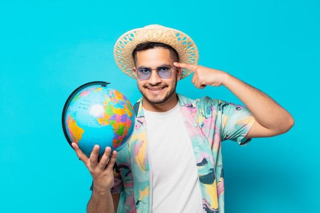 Jeune Homme Voyageur Hispanique Expression De Pensée Et Tenant Un Globe Terrestre Photo Premium