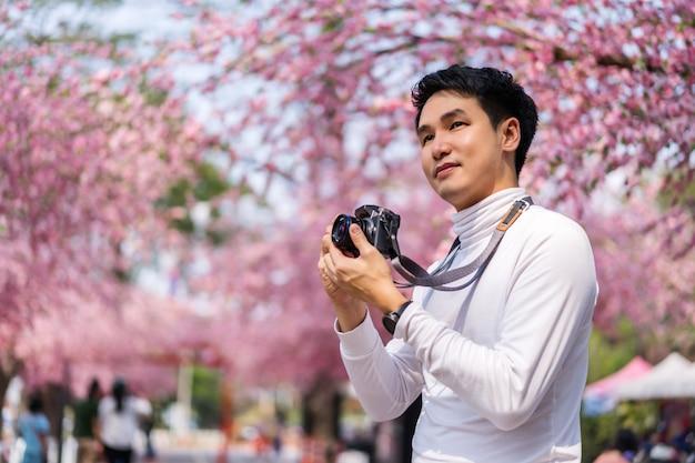 Jeune homme voyageur à la recherche de fleurs de cerisier ou de fleurs de sakura en fleurs et tenant l'appareil photo pour prendre une photo dans le parc