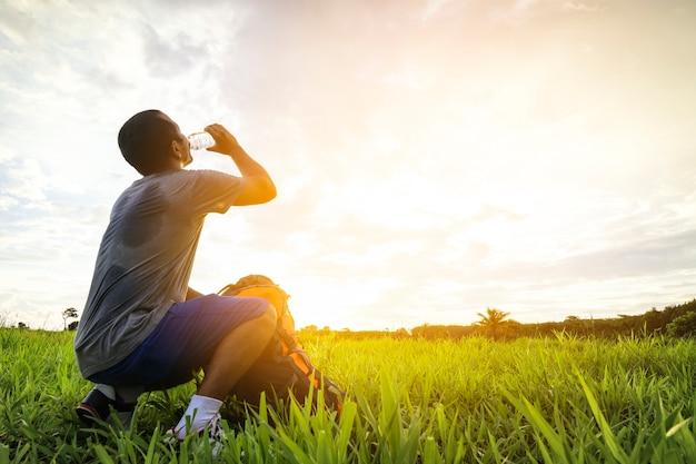 Jeune homme voyageur le sac à dos est de l'eau potable et regarde le coucher du soleil.