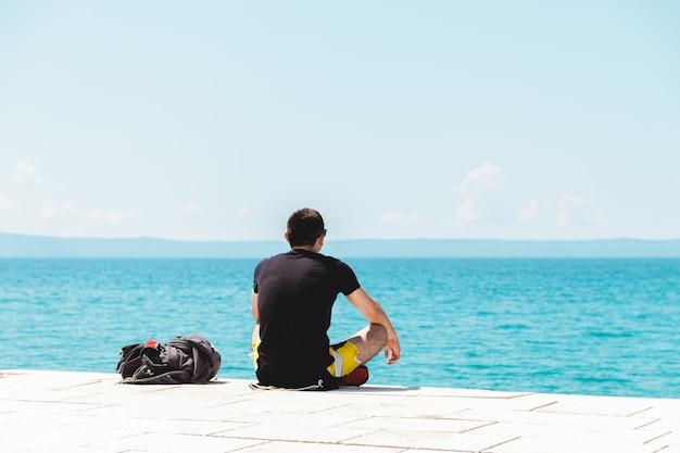 Jeune homme voyageur seul avec sac à dos près de lui méditant regardant dans l'océan et profitant du silence