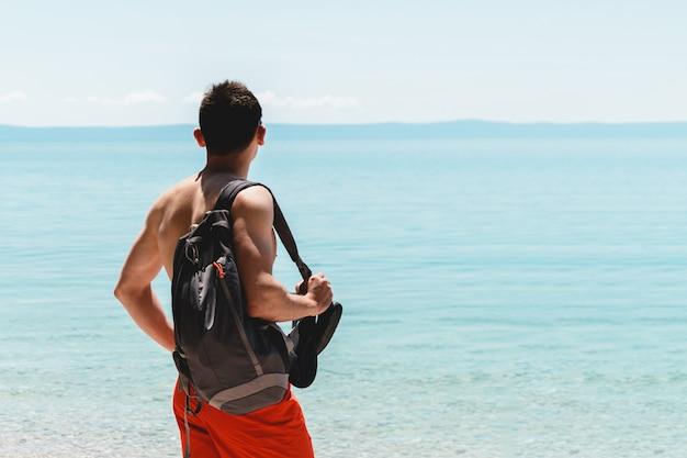 Jeune homme voyageur en short rouge avec sac à dos sur l'épaule au bord de la mer à la recherche de l'océan et profiter du silence. l'aventure commence