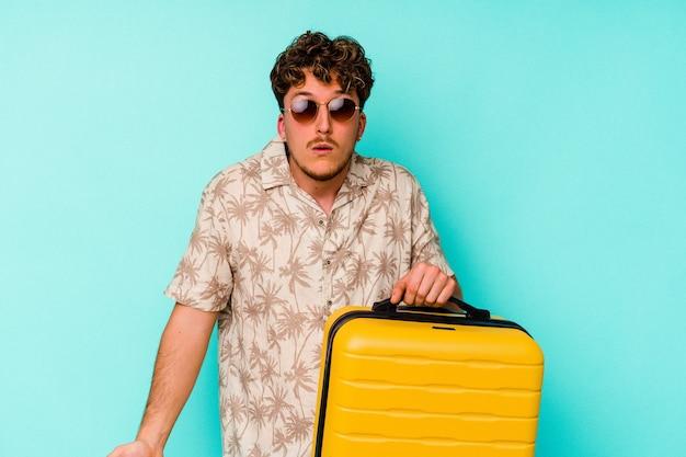 Jeune homme voyageur tenant une valise jaune sur fond bleu hausse les épaules et ouvre les yeux confus.