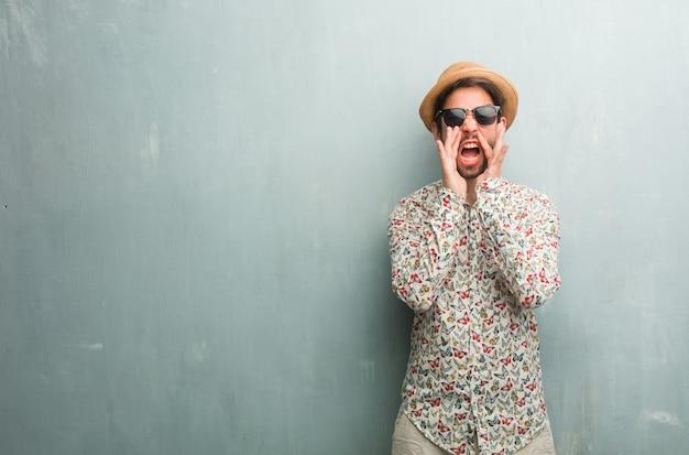 Jeune homme voyageur vêtu d'une chemise colorée hurlant de joie, surpris par une offre ou une promotion, béant, sautant et fier