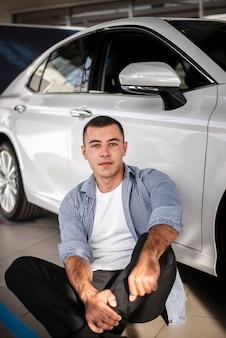 Jeune homme vue de face chez un concessionnaire automobile