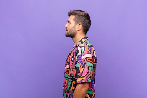 Jeune homme sur la vue de profil à la recherche de copier l'espace à venir, penser, imaginer ou rêver