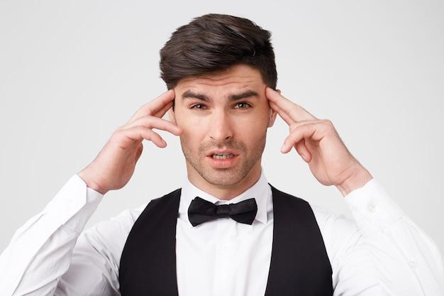 Jeune homme yeux concentrés pressé l'index près des tempes essayant de se souvenir de quelque chose, analyse approfondie de la situation
