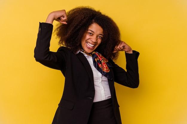 Jeune hôtesse de l'air afro-américaine isolée sur fond jaune montrant un geste de force avec les bras, symbole du pouvoir féminin