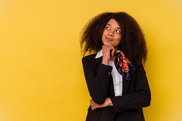 Jeune hôtesse de l'air afro-américaine isolée sur fond jaune regardant de côté avec une expression douteuse et sceptique.