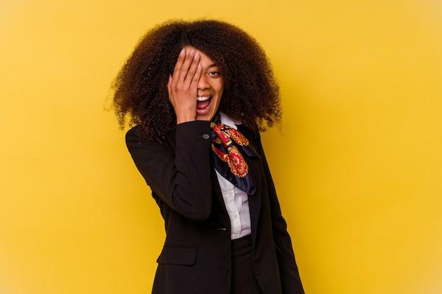 Jeune hôtesse de l'air afro-américaine isolée sur fond jaune s'amusant à couvrir la moitié du visage avec la paume.