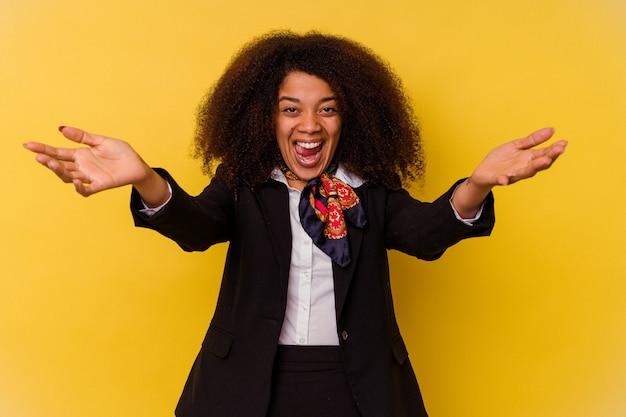 La jeune hôtesse de l'air afro-américaine isolée sur fond jaune se sent confiante en donnant un câlin à la caméra.