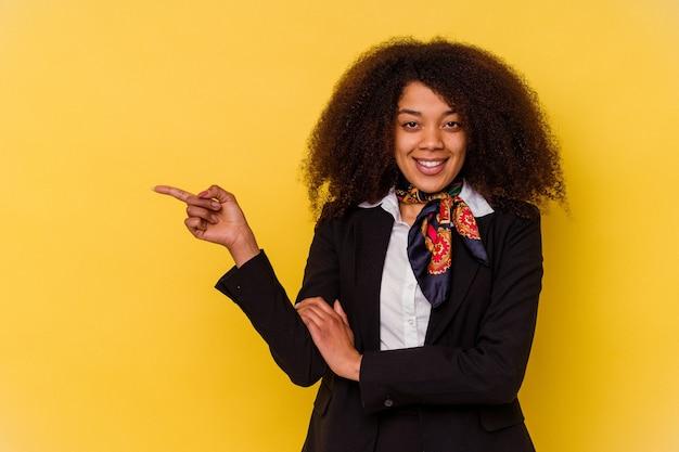 Jeune hôtesse de l'air afro-américaine isolée sur fond jaune souriant joyeusement pointant avec l'index loin.