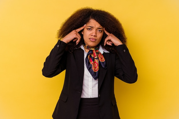 Jeune hôtesse de l'air afro-américaine isolée sur jaune concentrée sur une tâche, gardant les index pointés vers la tête.