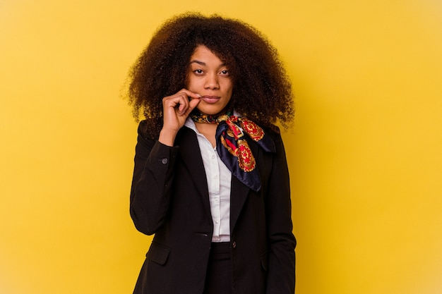 Jeune hôtesse de l'air afro-américaine isolée sur jaune avec les doigts sur les lèvres en gardant un secret.