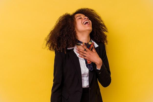 Jeune hôtesse de l'air afro-américaine isolée sur jaune éclate de rire en gardant la main sur la poitrine.