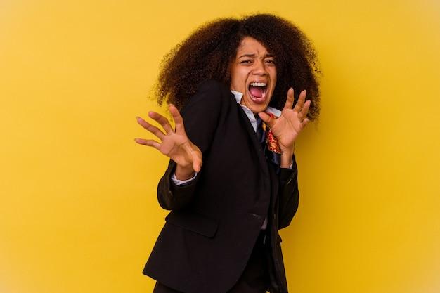 Jeune hôtesse de l'air afro-américaine isolée sur jaune étant choqué en raison d'un danger imminent