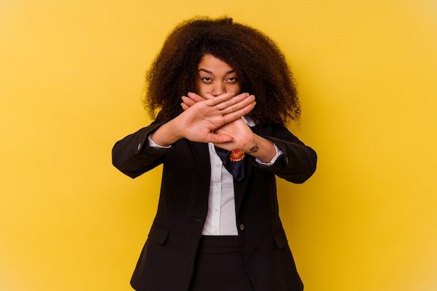Jeune hôtesse de l'air afro-américaine isolée sur jaune faisant un geste de déni