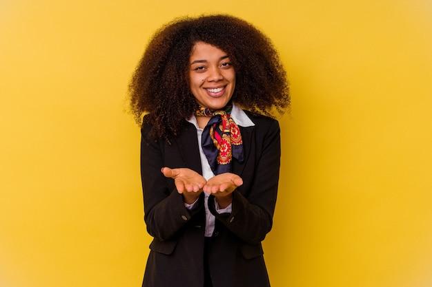 Jeune hôtesse de l'air afro-américaine isolée sur jaune tenant quelque chose avec des palmiers