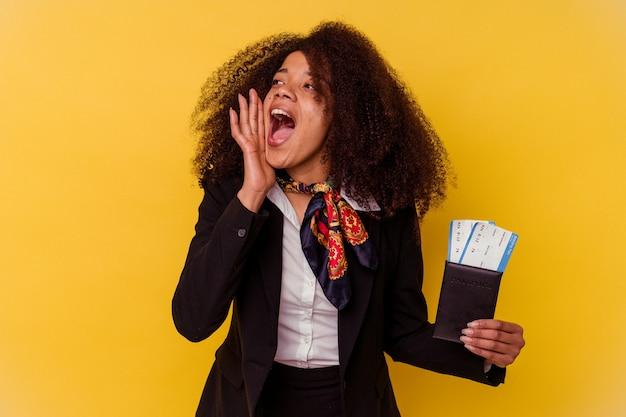 Jeune hôtesse de l'air afro-américaine tenant un billet d'avion isolé sur jaune criant et tenant la paume près de la bouche ouverte.
