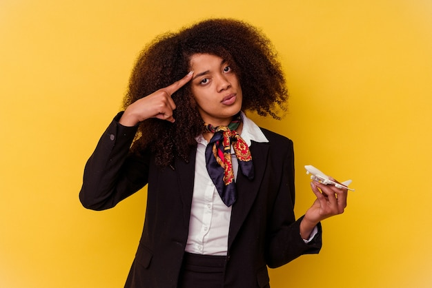 Jeune hôtesse de l'air afro-américaine tenant un petit avion isolé sur fond jaune pointant le temple avec le doigt, pensant, concentré sur une tâche.