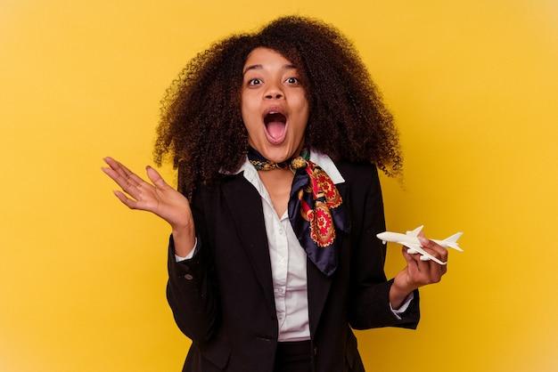 Jeune hôtesse de l'air afro-américaine tenant un petit avion isolé sur jaune surpris et choqué.