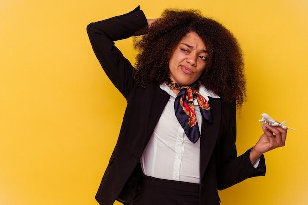Jeune hôtesse de l'air afro-américaine tenant un petit avion isolé sur jaune touchant l'arrière de la tête, en pensant et en faisant un choix.