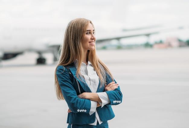 Jeune hôtesse de l'air en uniforme sur le parking des avions
