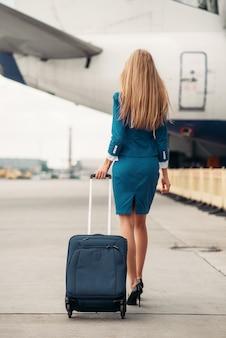 Jeune hôtesse de l'air avec valise sur le parking des avions