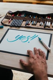 Jeune illustrateur hipster en tshirt simple noir crée un dessin de lettrage à la main authentique et unique dans son studio industriel lumineux