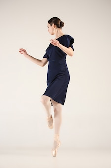 Jeune et incroyablement belle ballerine danse dans un studio bleu