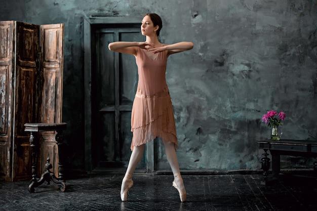 Jeune et incroyablement belle ballerine pose et danse dans un studio noir