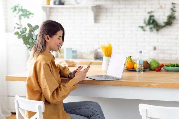 Jeune indépendante caucasienne assise à la maison dans la cuisine travaillant à distance
