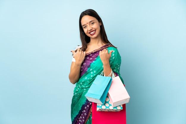 Jeune, indien, femme, achats, sacs, pouces, haut, geste, sourire