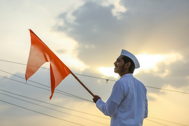 Jeune indien (pèlerin) en tenue traditionnelle et agitant un drapeau religieux.