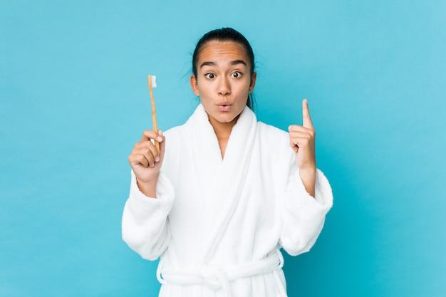 Jeune indien de race mixte tenant une brosse à dents ayant une excellente idée, concept de créativité.