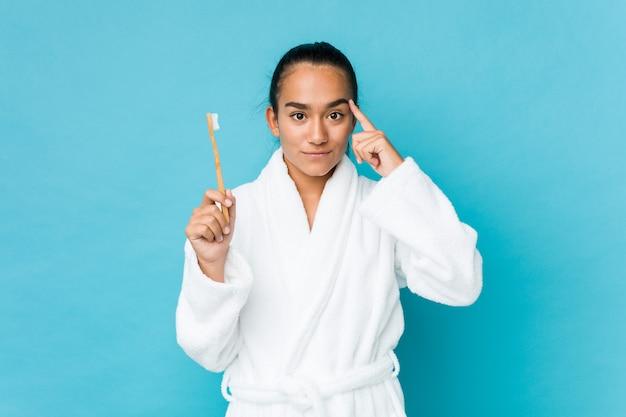 Jeune indien de race mixte tenant une brosse à dents pointant sa tempe avec le doigt, pensant, concentré sur une tâche.