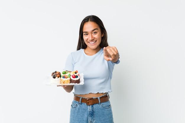 Jeune indien de race mixte tenant un gâteaux sucrés sourires gais pointant vers l'avant.