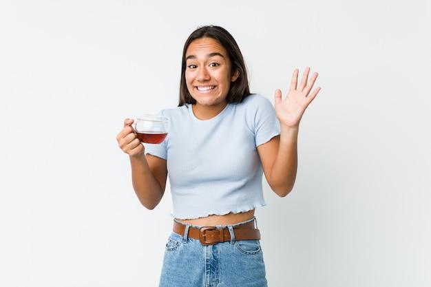 Jeune indien de race mixte tenant une tasse de thé célébrant une victoire ou un succès