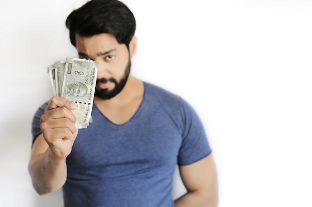 Jeune indien tenant beaucoup de 500 roupies dans ses mains.