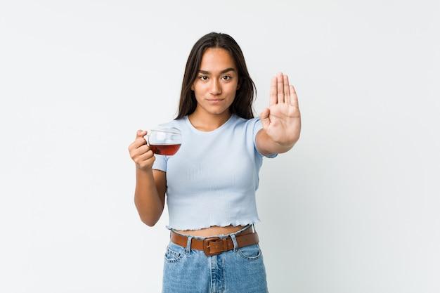 Jeune indien tenant une tasse de thé debout avec la main tendue montrant le panneau d'arrêt