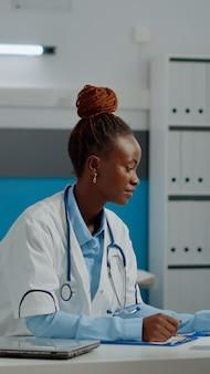 Jeune infirmier expliquant le résultat des rayons x au vieil homme au bureau